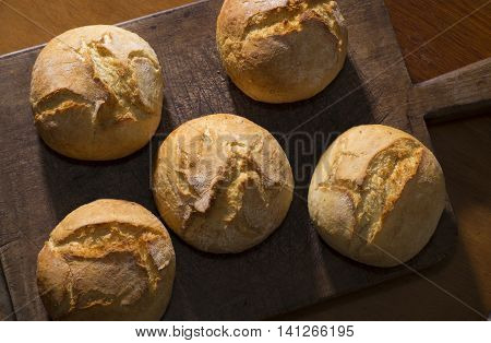 Traditional rustic buns on a vintage cutting board