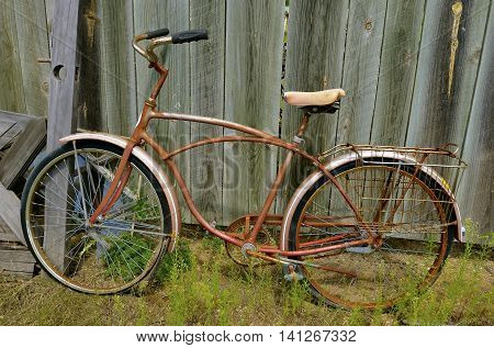 An old boy's bike with dual rear wire baskets leans against a weathered wooden fence.