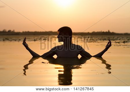 guy medidate; calmness of sunset on lake; quietness and tranquility;