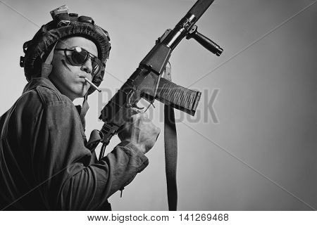Brave serious soldier with rifle posing over white background