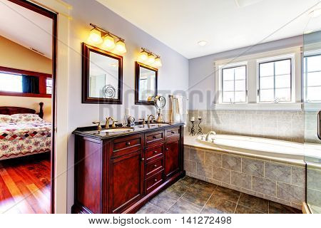 Nice Lavender Bathroom With Tub And Wood Cabinet With Two Sinks