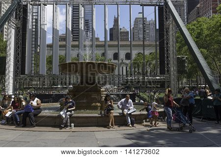 New York NY USA -- Aug 3 2016 New Yorkers enjoying Bryant Park on a sunny afternoon with view of skyscrapers in the background. Editorial Use Only