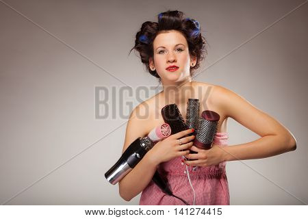 Young woman preparing for date having fun cute girl with curlers styling hair with many accessories comb brush hairdreyer on gray