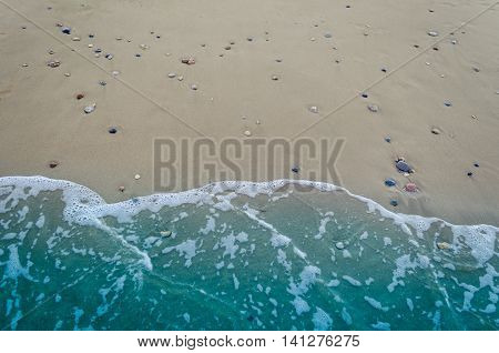 Wave of the sea on the sand beach. Sand and wave background. Soft wave of blue ocean on sandy beach. Sea wave over sand. Background of wave on the sand.