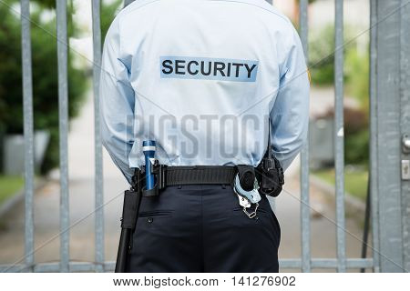 Rear View Of A Security Guard Standing In Front Of Gate
