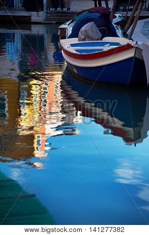 Boat on water and reflection, Burano, Italy