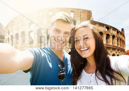 Portrait Of A Young Happy Couple In Front Of Coliseum
