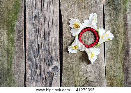 Coral Bracelet On A Background Of White Flowers On The Old Floor