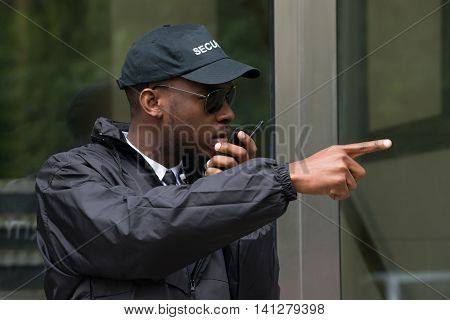 Young Male Security Guard Gesturing While Talking On Walkie-Talkie