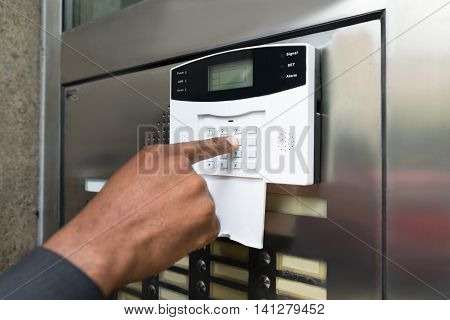 Close-up Of Businessperson's Hand Entering Code In Security System