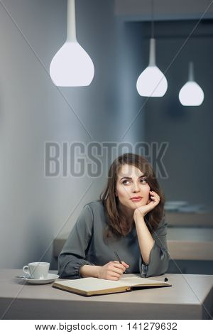 Young Adult Female Has Coffee Break In Cafe And Writing Notes In Diary Or Notepad;
