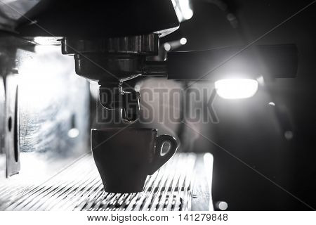 silhouette of coffee making process; espresso cup and coffee machine; artistic shot of hot beverage brewing;