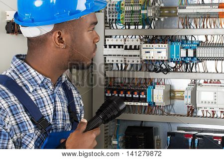 Young African Male Technician Analyzing Fusebox With Flashlight