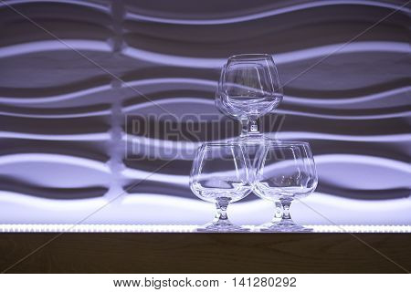 brandy glasses pyramid on the purple background; set of alcohol glassed near backlighted wall;