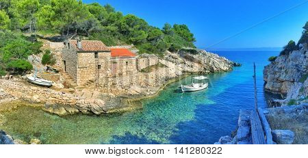 Remote bay with old stone houses and old fishing boat on the island of Lastovo, Croatia.