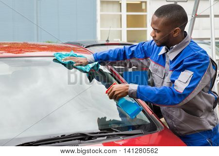 Young African Worker Wiping Car Windshield With Cloth