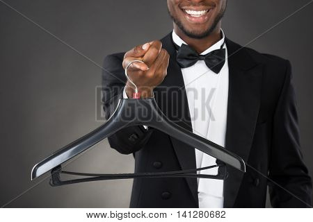 Portrait Of Happy Male Housekeeper Holding Plastic Hanger