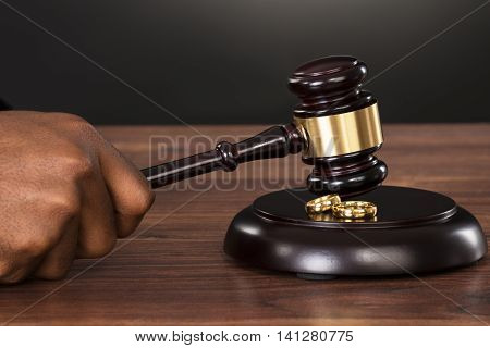 Close-up Of A Judge Hands Hitting Gavel With Golden Rings At Desk