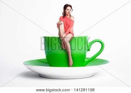 Small Female Sitting On Giant Coffee Cup; Woman On Diet,