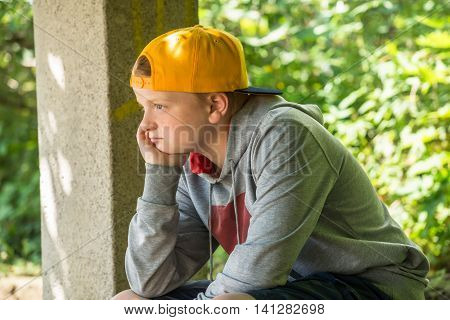 Upset Boy Sitting In Park With Hand On Head