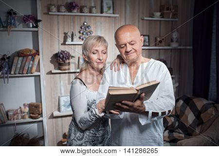 Happy Seniors Couple Embrace And Read Book;