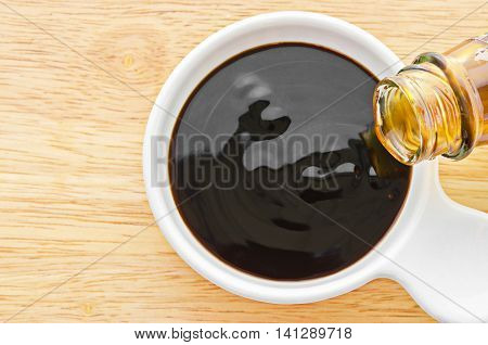 Oyster sauce in white bowl on wooden background.