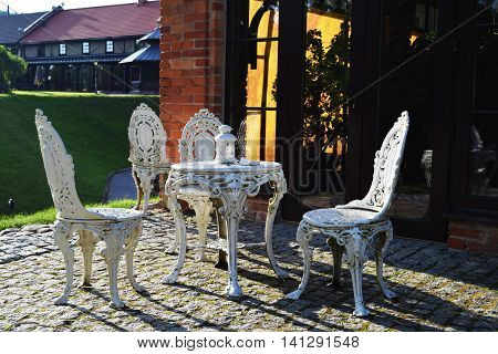 White metallic vintage furniture in the park, table and chairs