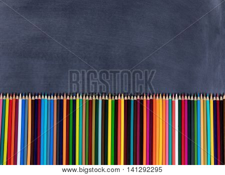 Overhead view of colorful pencils lined up on bottom of erased chalkboard.