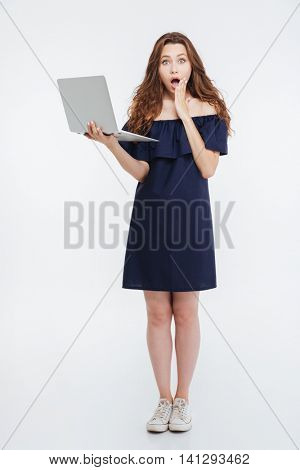 Full length of amazed attractive young woman standing and holding laptop over white background