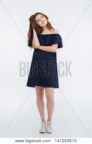 Thoughtful frowning young woman standing and thinking over white background