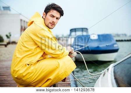 Handsome young sailor in yellow cloak holding rope at the pier and looking at camera