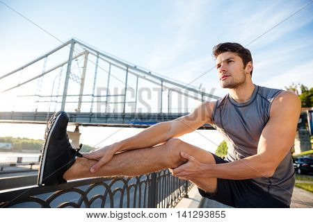 Handsome young sports man doing stretching leaning against bridge railing and looking away outdoors