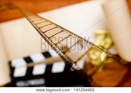 Film on the background of a movie clapper on a wooden table