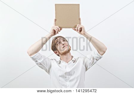 Young Adult Man in White Shirt Holding a Big Cardboard Inscription Above His Head, Looking Up at It