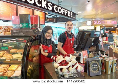 SINGAPORE - CIRCA NOVEMBER, 2015: Starbucks workers at Singapore Changi Airport. Starbucks Corporation is an American global coffee company and coffeehouse chain.