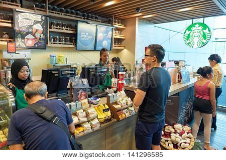SINGAPORE - CIRCA NOVEMBER, 2015: customer in Starbucks at Singapore Changi Airport. Starbucks Corporation is an American global coffee company and coffeehouse chain.