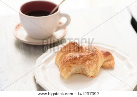 Bited Croissant And Coffee Cup