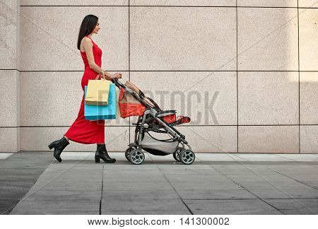 walking young mother with baby carriage along the wall on city street
