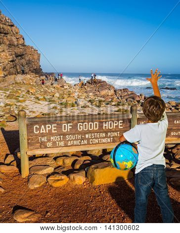 The seven-year-old boy with the globe an armpit is delighted with a picturesque landscape.  Cape of Good Hope - the most extreme south-western point of Africa. The powerful ocean surf in the Atlantic