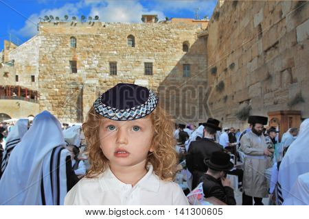The lovely little boy with long light curls and blue eyes in a knitted skullcap. It costs at the main Jewish shrine - the Western wall of the Temple. Jewish holiday of Sukkot