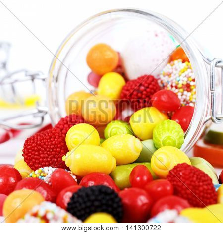 many different colorful candies and chewing gum scattered on the table on white background
