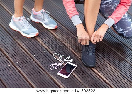 Active runners girls with smartphone and and headphones, tying running shoes laces. Healthy lifestyle, fitness, sport, training, technology concept. Female athletes exercising.