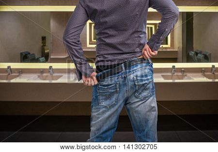 Man Adjusts After Peeing On The Public Toilet