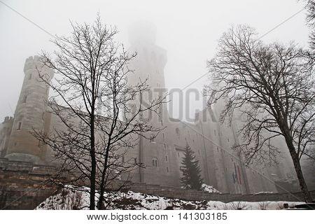 Hohenschwangau Germany - April 06 2012: Neuschwanstein Castle in the mist of late winter. Snow still