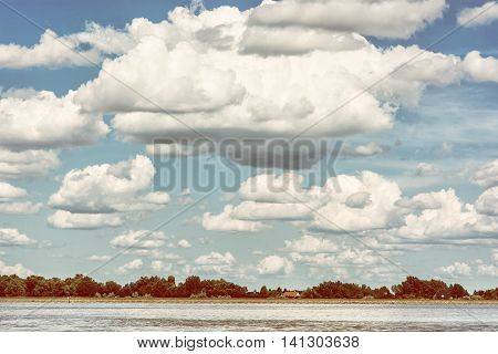 Waterfront with trees and house and blue sky with big clouds. Danube river. Photo filter. Natural scene. Beauty in nature. Travelling theme. Summer vacation.