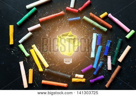 Idea inspiration concepts, colorful chalks on chalkboard with bright light bulb made of crumpled paper ball at center
