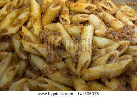 This is a photograph of Penne Pasta covered in Tomato sauce and ground beef