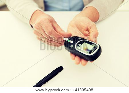 medicine, age, diabetes, health care and people concept - close up of senior woman with glucometer and test stripe checking blood sugar level at home