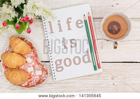 Breakfast and an inscription in a notepad: Life is good. Top view