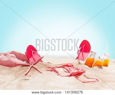 Holiday Accessories on Sand Beach Orange Juice Bikini Slippers Sea Star Sunny Summer Day Relax Concept Art Collage isolated Blue Background